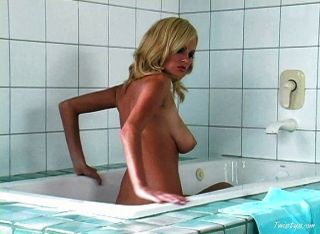 Chica rubia caliente tomando un baño
