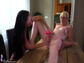 Anciana y linda chica masturbándose con consolador sobre el escritorio