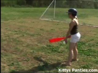 Inocente gatito adolescente jugando softball al aire libre