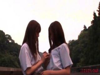 2 colegialas besando caricias mientras está de pie al aire libre