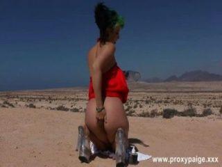 Desierto en vestido rojo y botella grande en culo (2014)