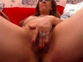 Mujer madura con gafas juega con su coño peludo