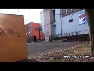 chica aficionada se esconde detrás de una pared para tomar un pis