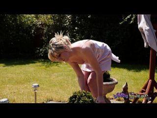 exhibicionista rubia se toma el sol topless por su remolque arbusto para 4k video