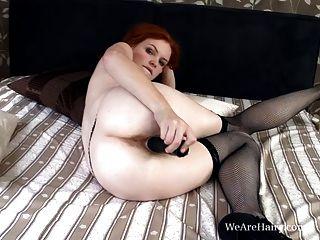 Florencia peluda empuja un consolador en su coño peludo rojo