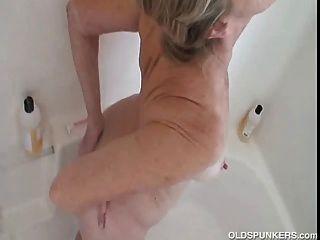 Hermosa abuela se pone agradable y húmedo y jabón en la ducha