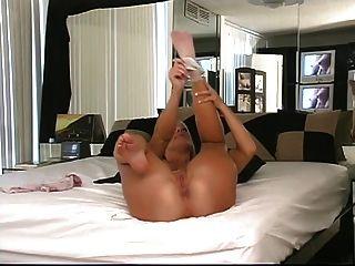 Rubia se pone de rodillas en la cama para mostrar su culo redondo