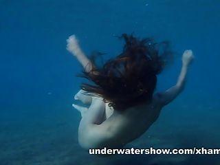 Julia está nadando bajo el agua desnuda en el mar