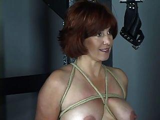 Pelirroja desnuda con tetas bonitas y culo es azotado en bdsm mazmorra