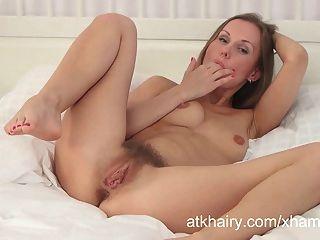 Lera se masturba en una cama blanca