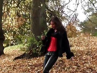 Muchacha caliente que camina en leatherfetish panty, corsé y cargadores rojos