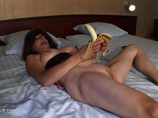 Afeitado madre madura se masturba con el plátano