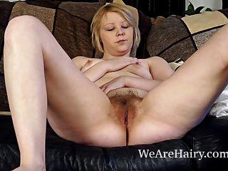Danniella juega con su coño peludo en el sofá