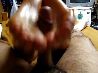 Chica rubia dando un footjob reverso con pies aceitosos