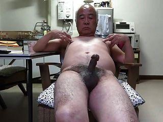 Contracción del pene del hombre viejo japonés a los pezones del tacto