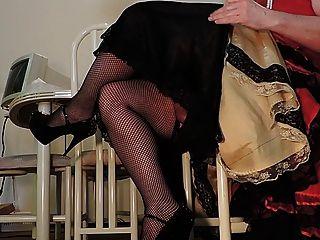 Rayo de sissy en el vestido rojo y las medias del fishnet