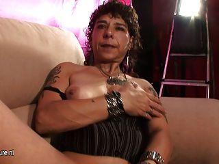 Vieja madre brutal se masturba en el sofá de fundición