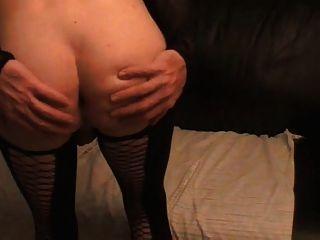 Tara crossdress está posando en medias de nilones negro y muestra culo