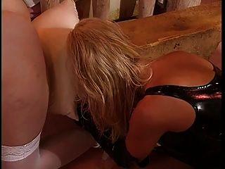 Tetas grandes, señora lesbiana vestida de cuero disfrutando con su esclavo