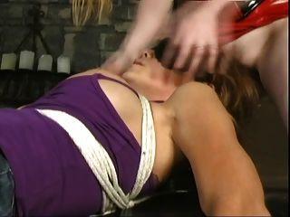 Cara lesbiana que se sienta en la muchacha bondaged