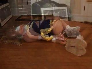 Rubia cheerleader hogtied y cinta adhesiva amordazada