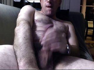 Papá caliente masturbándose en el sofá