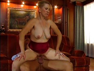 Sexy mamá n77 rubia madura en un sofá rojo