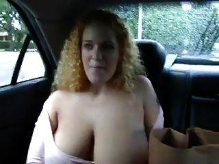 Busty pelirroja muestra sus tetas en el asiento trasero de un coche
