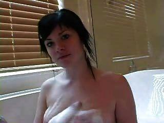 Hermosa chica tatuada en un baño de burbujas
