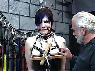 Hermosa joven con los ojos vendados morena en corsé es torturada por el maestro len
