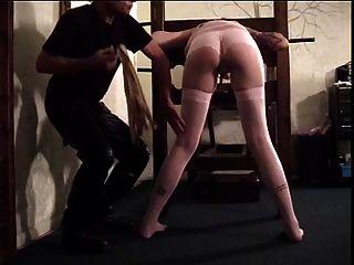 Hottie de pelo oscuro obtiene su culo azotado por una paleta