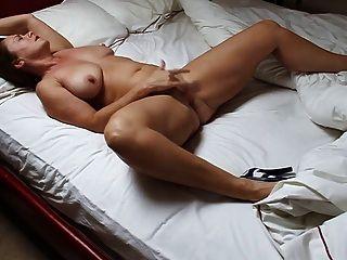 Hermosa mujer madura masturbándose en la cama