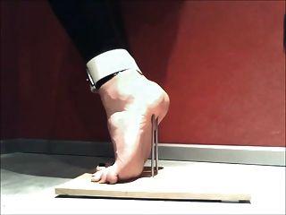 Tortura de pie para ponerse de puntillas con uñas y atado
