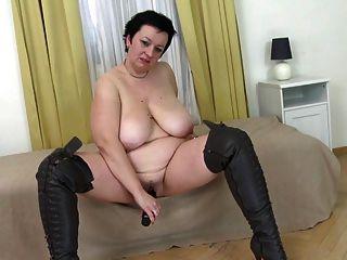 Mamá pechugona grande en botas de cuero folla su coño