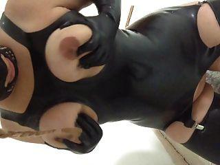 Mujer de puta de látex ordeñando sus tetas esclavo