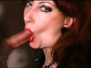Madura pelirroja con lápiz labial rojo y chupar polla