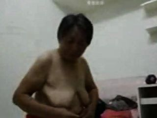 La abuela asiática se viste después del sexo