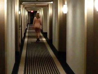 Sexy MILF en talones caminando desnuda en el pasillo del motel