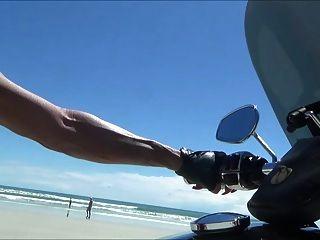 Motociclista de cuero sexy en botas de muslo en la playa