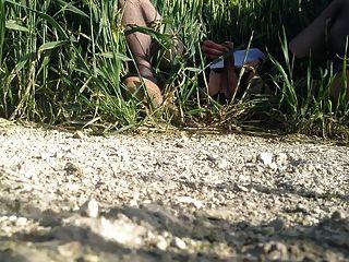 crossdresser masturbándose en un campo de trigo