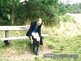 pelirroja en botas destellando al aire libre