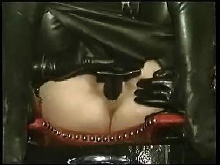 señora en látex tiene pantalones consolador interno quitado