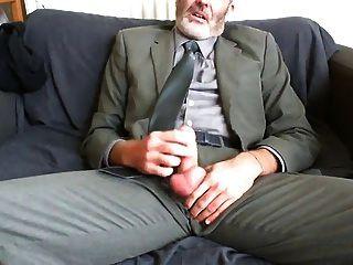 papá barbudo sexy después de traje de trabajo y alivio de lazo en el sofá
