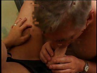 una chica sexy con la correa del juguete del sexo encendido y un individuo que chupa el juguete del sexo en el cuarto de baño