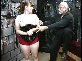 joven esclava bdsm morena en corsé es azotado y caned en el sótano
