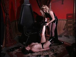 amante rubia bloquea a su esclavo en un pecho