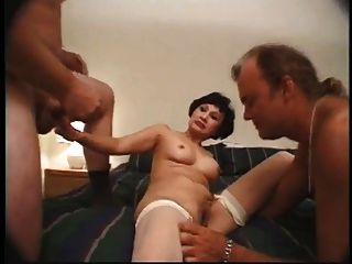 mujer asiática madura acaricia a dos hombres en la cama del hotel