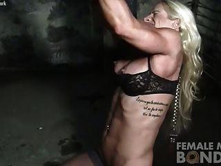 bodybuilder femenino en cadenas en la mazmorra