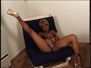 sexy ébano en tacones dedos su jugoso coño en una silla