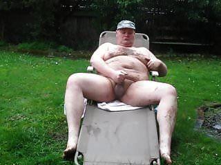 hombre gordo en la lluvia y el barro